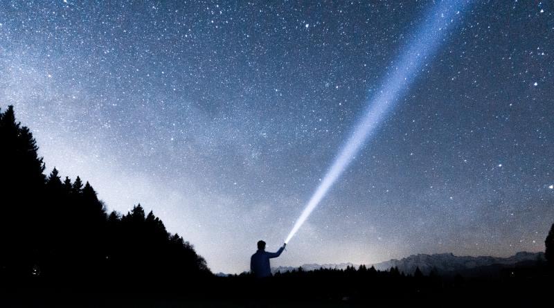 Eine LED Taschenlampe leuchtet in den Nachthimmel