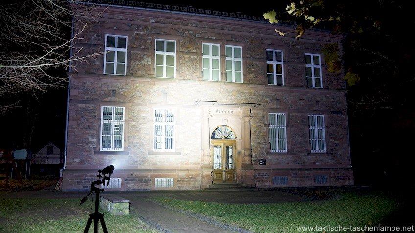 LED Taschenlampe Acebeam K30 leuchtet ein Gebäude an.