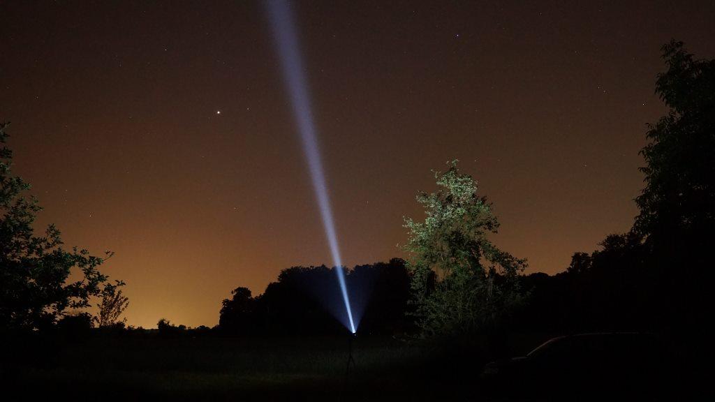 Thrower Taschenlampe leuchtet in Nachthimmel