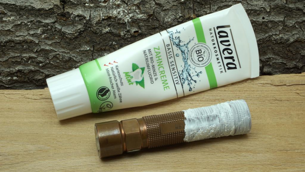Taschenlampe aus Kupfer während der Reinigung mit Zahnpasta