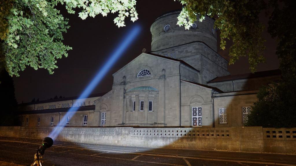 Der Astrolux MF04 Thrower leuchtet an einem Gebäude vorbei in den Nachthimmel