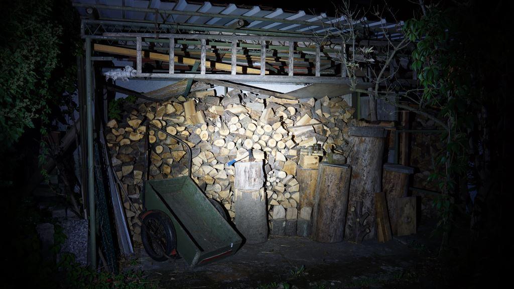 Klarus XT1A Beamshot vor Holzschuppen