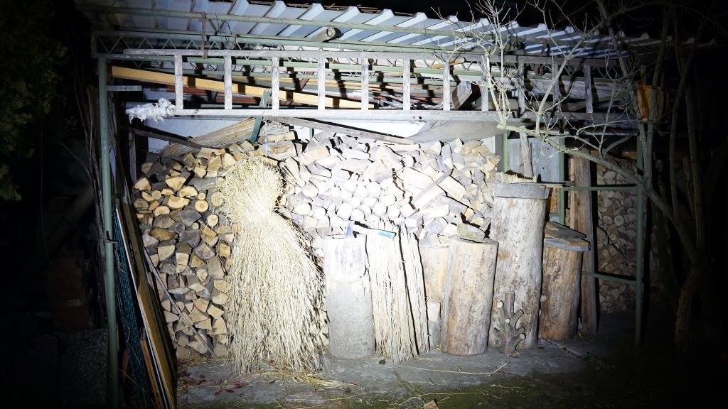 Nextorch Saint Torch 30 leuchtet in einen Holzschuppen